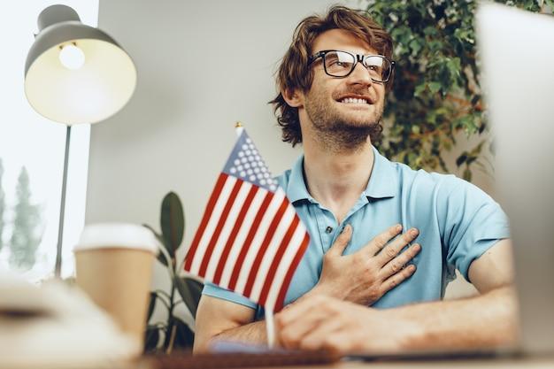 Młody brodaty mężczyzna siedzi przy stole z laptopem i amerykańską flagą