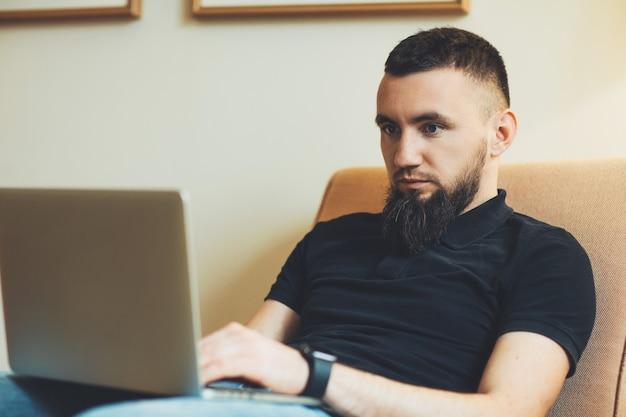 Młody brodaty mężczyzna siedzi w kanapie i patrząc na laptopa trzymając go na nogach w domu. mężczyzna freelancer pracuje na swoim laptopie w domu.