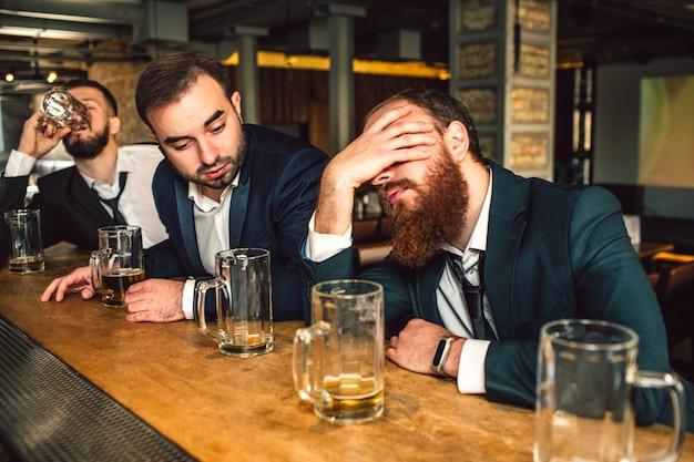 Młody brodaty mężczyzna siedzieć z przodu i spać. on jest pijany. drugi młody człowiek patrzy na niego. po trzecie pić piwo.