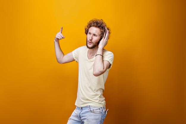 Młody brodaty mężczyzna słucha muzyka z palcem up