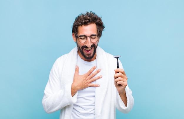 Młody brodaty mężczyzna śmieje się głośno z jakiegoś przezabawnego żartu, czuje się szczęśliwy i wesoły, dobrze się bawi