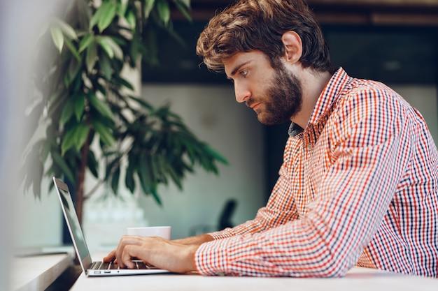 Młody brodaty mężczyzna sobie dorywczo koszulę przy użyciu swojego laptopa. portret biznesmena