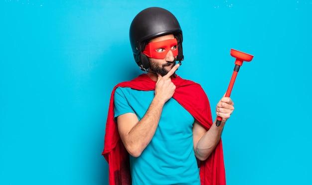 Młody brodaty mężczyzna. szalony i pełen humoru super bohater z kaskiem i maską