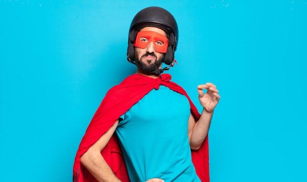 Młody brodaty mężczyzna. szalony i pełen humoru superbohater z kaskiem i maską