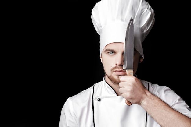 Młody brodaty mężczyzna szef kuchni w białym mundurze trzyma nóż przed twarzą na czarnym tle