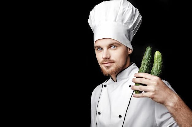 Młody brodaty mężczyzna szef kuchni w białym mundurze trzyma ogórek na czarnym tle
