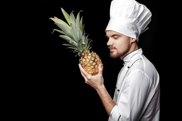 Młody brodaty mężczyzna szef kuchni w białym mundurze trzyma świeżego ananasa na czarnym tle