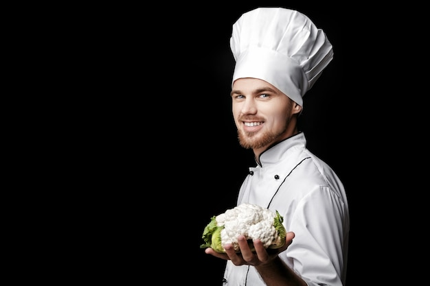 Młody brodaty mężczyzna szef kuchni w białym mundurze trzyma świeży kalafior na czarnym tle