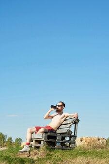 Młody brodaty mężczyzna topless pije piwo siedząc na drewnianej ławce na zewnątrz na tle jasnego nieba