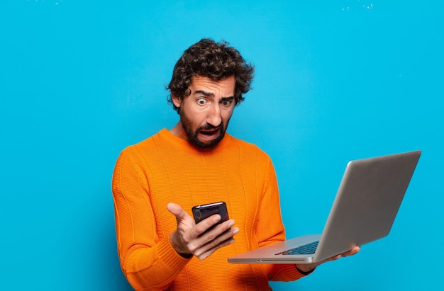 Młody brodaty mężczyzna trzyma laptopa. koncepcja mediów społecznościowych