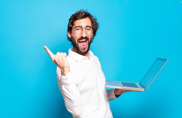 Młody brodaty mężczyzna trzyma laptopa