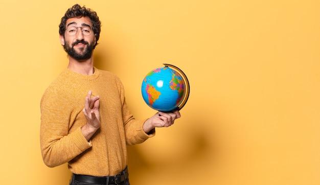 Młody brodaty mężczyzna trzyma mapę świata.