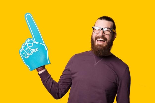 Młody brodaty mężczyzna trzyma rękawicę wentylatora skierowaną w górę i uśmiecha się, patrząc w kamerę w pobliżu żółtej ściany