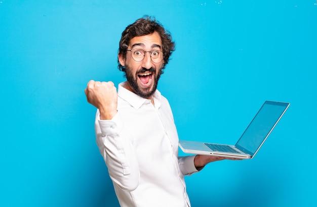 Młody brodaty mężczyzna trzymający laptopa