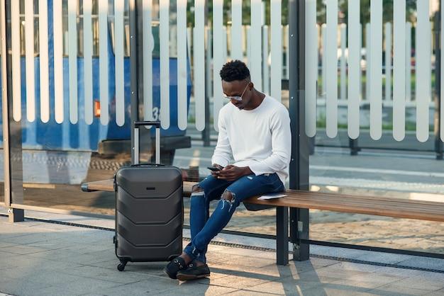 Młody brodaty mężczyzna turysta z plecakiem i smartfonem