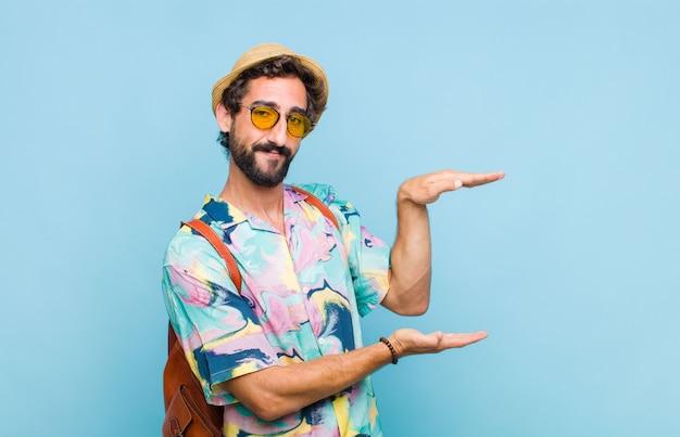 Młody brodaty mężczyzna turystyczny trzymający przedmiot obiema rękami na bocznej przestrzeni kopii, pokazując, oferując lub reklamując obiekt