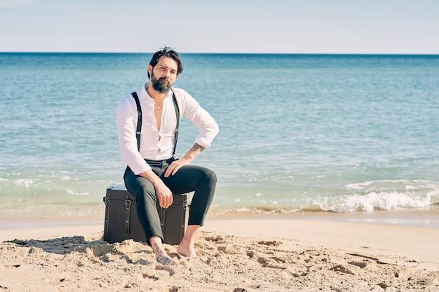 Młody brodaty mężczyzna ubrany jak pan młody siedzi na plaży