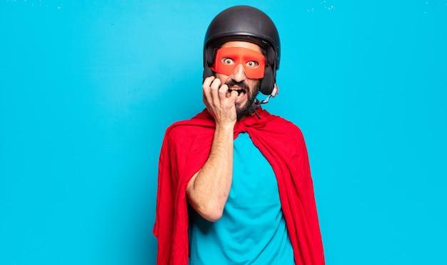 Młody brodaty mężczyzna ubrany w kostium superbohatera z hełmem i maską