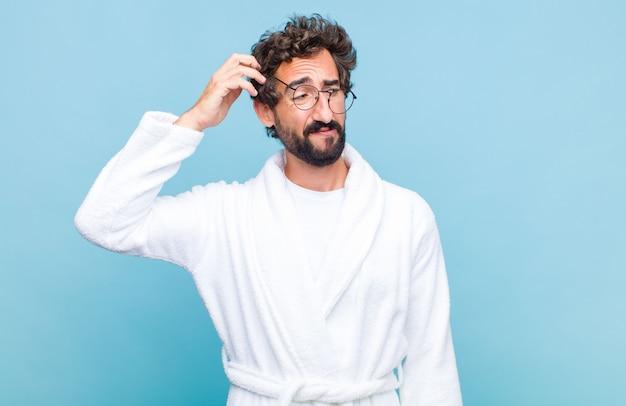 Młody brodaty mężczyzna ubrany w szlafrok czuje się zdziwiony i zdezorientowany, drapiąc się po głowie i spoglądając w bok