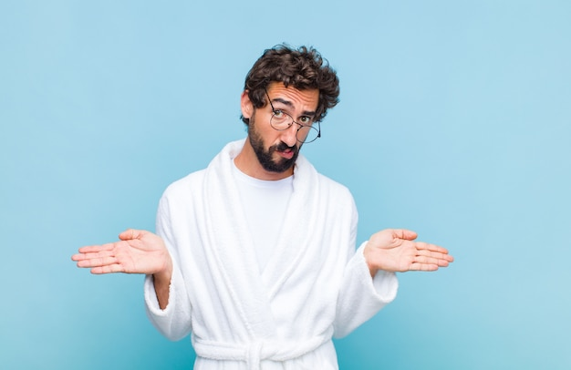 Młody brodaty mężczyzna ubrany w szlafrok czuje się zdziwiony i zdezorientowany