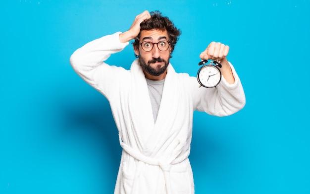 Młody brodaty mężczyzna ubrany w szlafrok i budzik