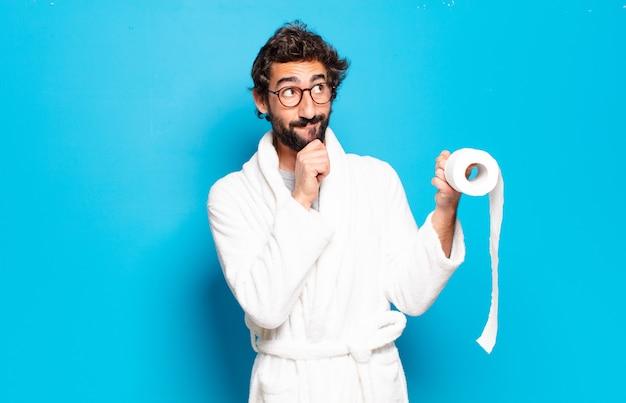 Młody brodaty mężczyzna ubrany w szlafrok i rolę toalety