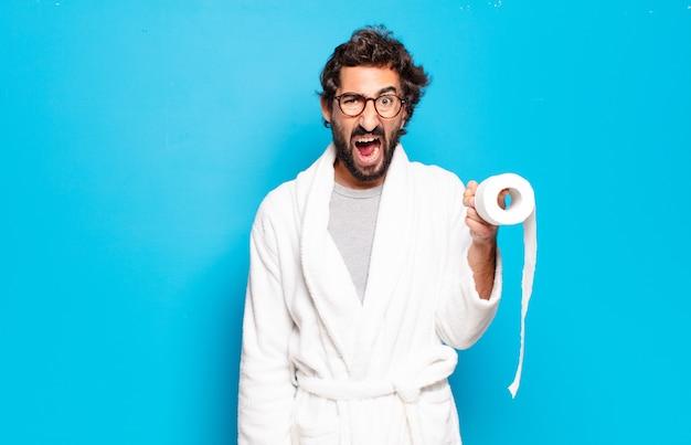 Młody brodaty mężczyzna ubrany w szlafrok i rolkę papieru toaletowego