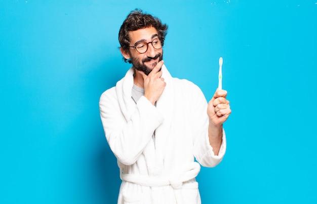Młody brodaty mężczyzna ubrany w szlafrok i szczoteczkę do zębów