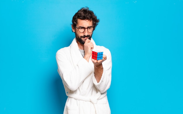 Młody brodaty mężczyzna ubrany w szlafrok rozwiązuje problem inteligencji