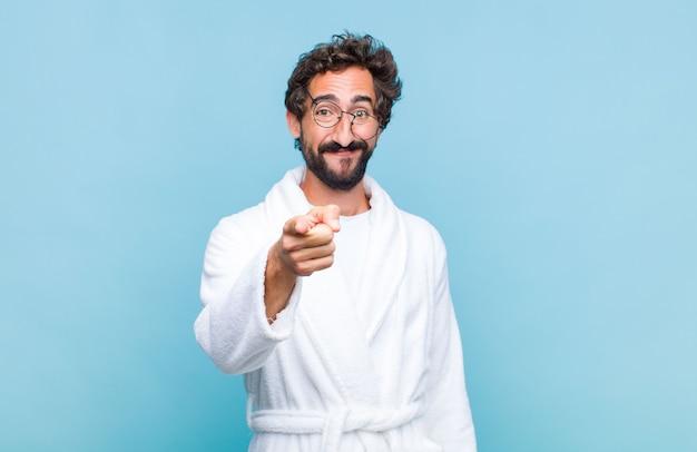 Młody brodaty mężczyzna ubrany w szlafrok, wskazując na aparat z zadowolonym, pewnym siebie, przyjaznym uśmiechem, wybierając cię
