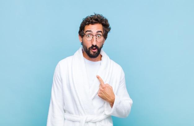 Młody brodaty mężczyzna ubrany w szlafrok wygląda na zszokowanego i zaskoczonego z szeroko otwartymi ustami, wskazując na siebie