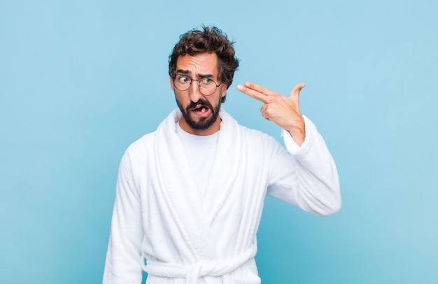 Młody brodaty mężczyzna ubrany w szlafrok wyglądający na nieszczęśliwego i zestresowanego, gest samobójczy robiący znak pistoletu ręką, wskazujący na głowę