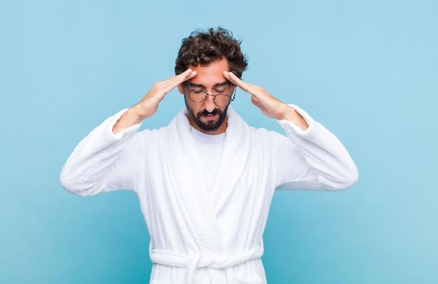 Młody brodaty mężczyzna ubrany w szlafrok wyglądający na skoncentrowanego, zamyślonego i zainspirowanego, burzy mózgów i wyobraźni z rękami na czole