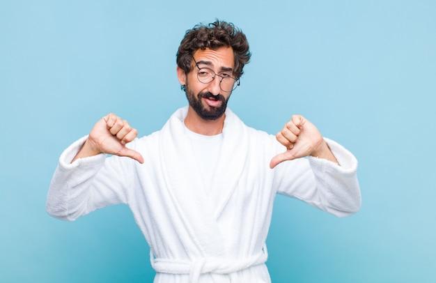 Młody brodaty mężczyzna ubrany w szlafrok wyglądający na smutnego, rozczarowanego lub złego, pokazujący kciuki w dół w niezgodzie, sfrustrowany