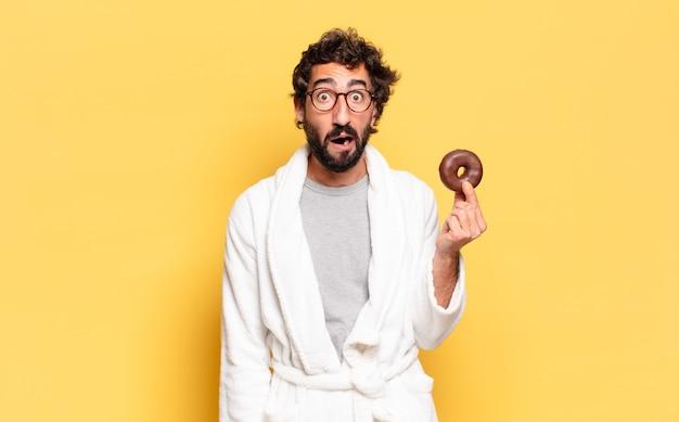 Młody brodaty mężczyzna ubrany w szlafrok z czekoladowym pączkiem