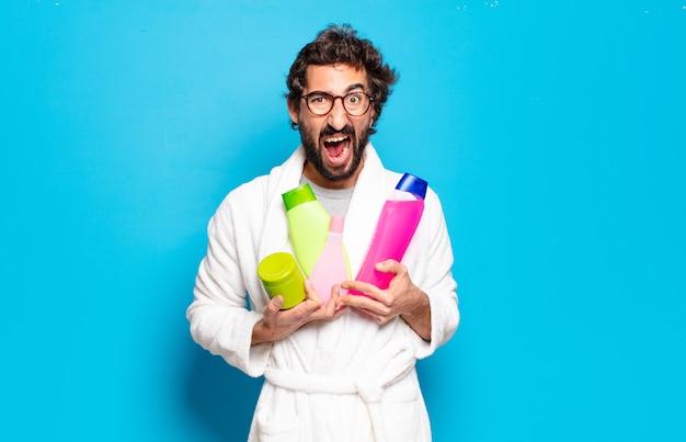 Młody brodaty mężczyzna ubrany w szlafrok z szamponem i kosmetykami
