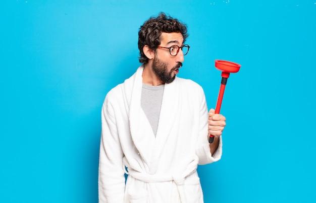Młody brodaty mężczyzna ubrany w szlafrok z tłokiem