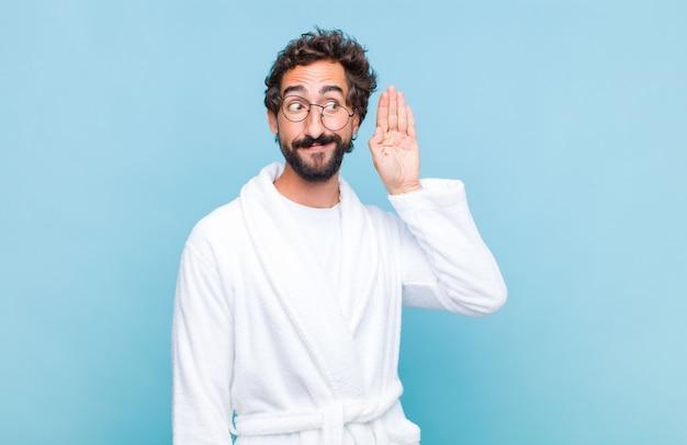Młody brodaty mężczyzna ubrany w szlafrok z uśmiechem