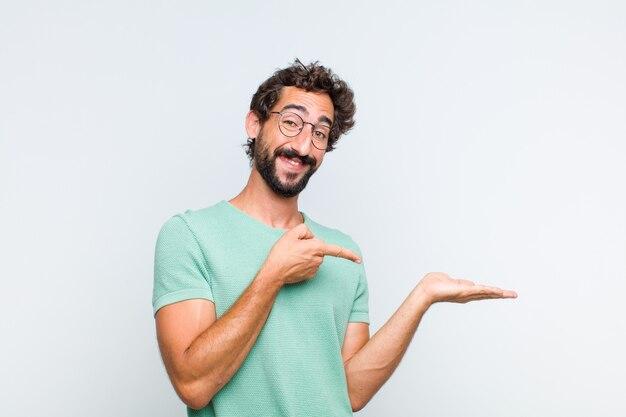 Młody brodaty mężczyzna uśmiecha się, czuje się szczęśliwy, beztroski i zadowolony, wskazując na koncepcję lub pomysł na kopię miejsca z boku