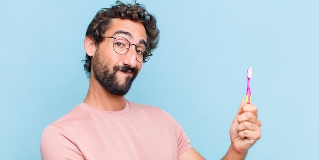 Młody brodaty mężczyzna uśmiecha się, czuje się szczęśliwy, pozytywny i zadowolony, trzyma lub pokazuje przedmiot lub koncepcję na przestrzeni kopii