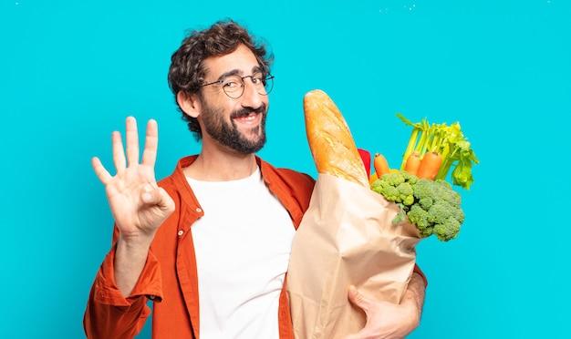 Młody brodaty mężczyzna uśmiecha się i wygląda przyjaźnie, pokazując numer cztery lub czwarty z ręką do przodu, odliczając i trzymając worek warzyw