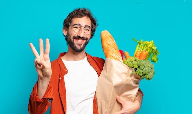 Młody brodaty mężczyzna uśmiecha się i wygląda przyjaźnie, pokazując numer trzy lub trzeci z ręką do przodu, odliczając i trzymając worek warzyw