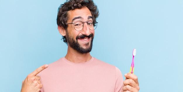 Młody brodaty mężczyzna uśmiecha się pewnie, wskazując na swój szeroki uśmiech, pozytywne, zrelaksowane, zadowolone nastawienie