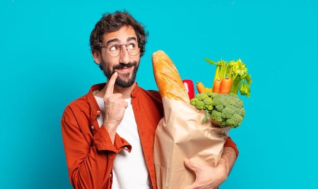 Młody brodaty mężczyzna uśmiecha się radośnie i marzy lub wątpi, patrząc z boku i trzymając worek warzyw