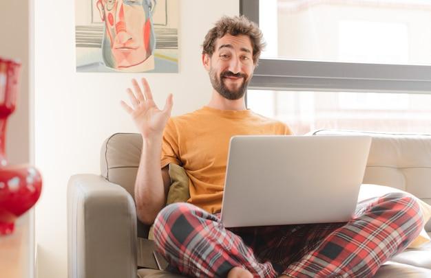 Młody brodaty mężczyzna uśmiecha się radośnie i wesoło macha ręką i wita lub żegna się i siedzi z laptopem