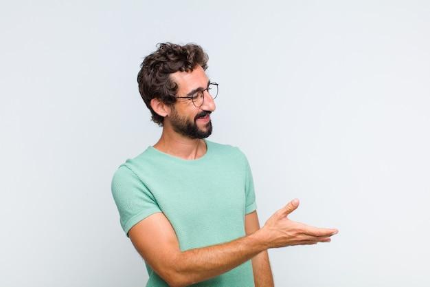 Młody brodaty mężczyzna uśmiecha się, wita i oferuje uścisk dłoni, aby zamknąć udaną transakcję, koncepcja współpracy