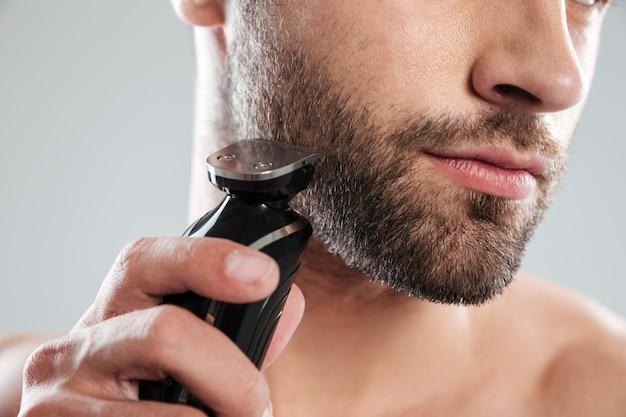 Młody brodaty mężczyzna używa elektryczną golarkę