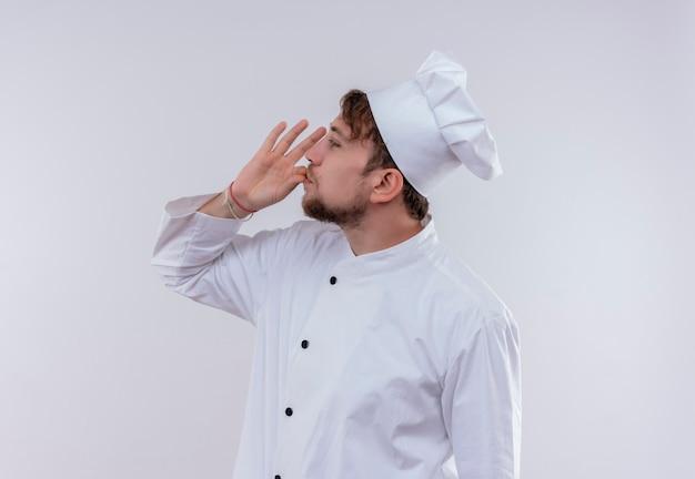 Młody brodaty mężczyzna w białym mundurze, patrząc z boku i trzymając rękę na ustach na białej ścianie