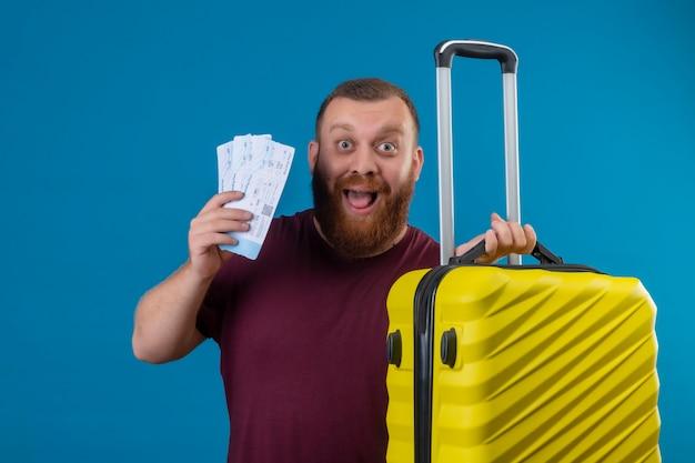 Młody brodaty mężczyzna w brązowej koszulce, trzymając walizkę podróżną i bilety lotnicze, patrząc podekscytowany i szczęśliwy