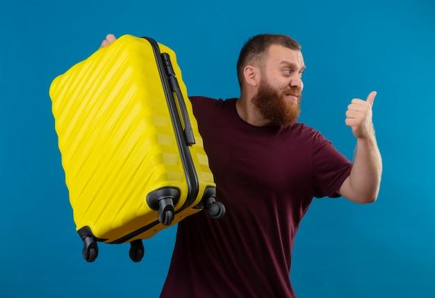 Młody brodaty mężczyzna w brązowej koszulce, trzymając walizkę podróżną, uśmiechając się, wskazując kciukiem z powrotem